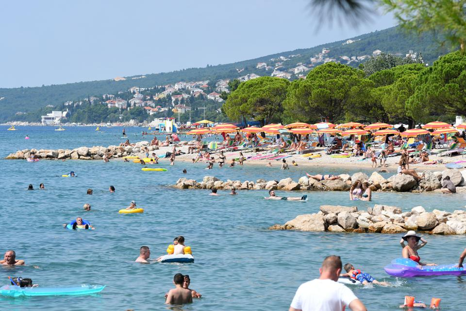 tourists sunbath and swim on Croatia's Adriatic coast but now face UK quarantine on return