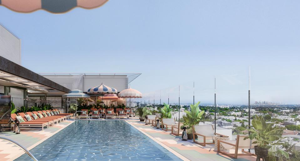 The Britley rooftop pool with colorful striped cabanas, blue water and a view of the city.