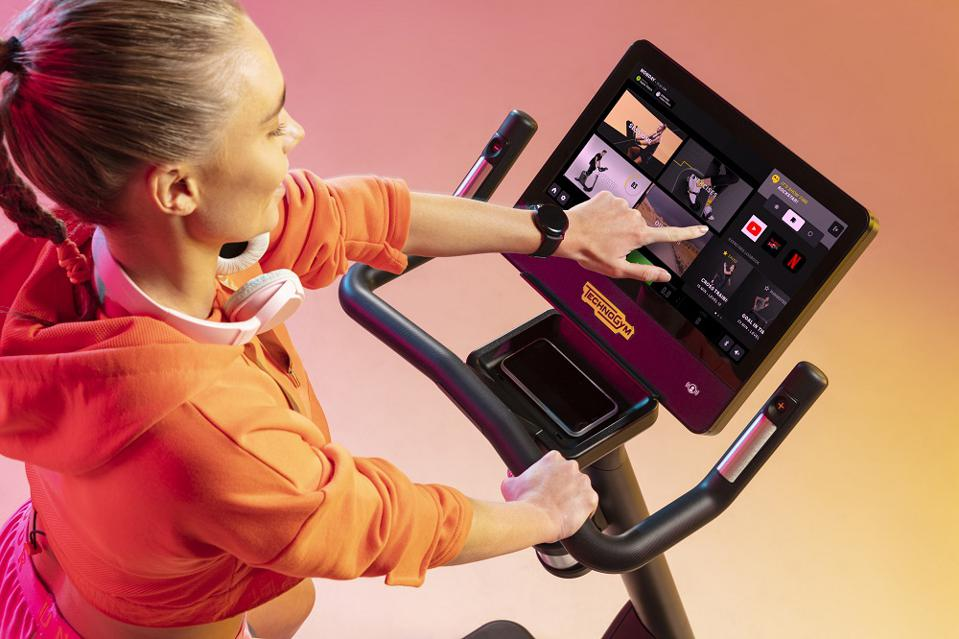 Woman working out on Technogym gym machine.