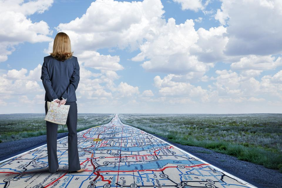 Businesswoman Stands On Long Road With Road Map Painted On It