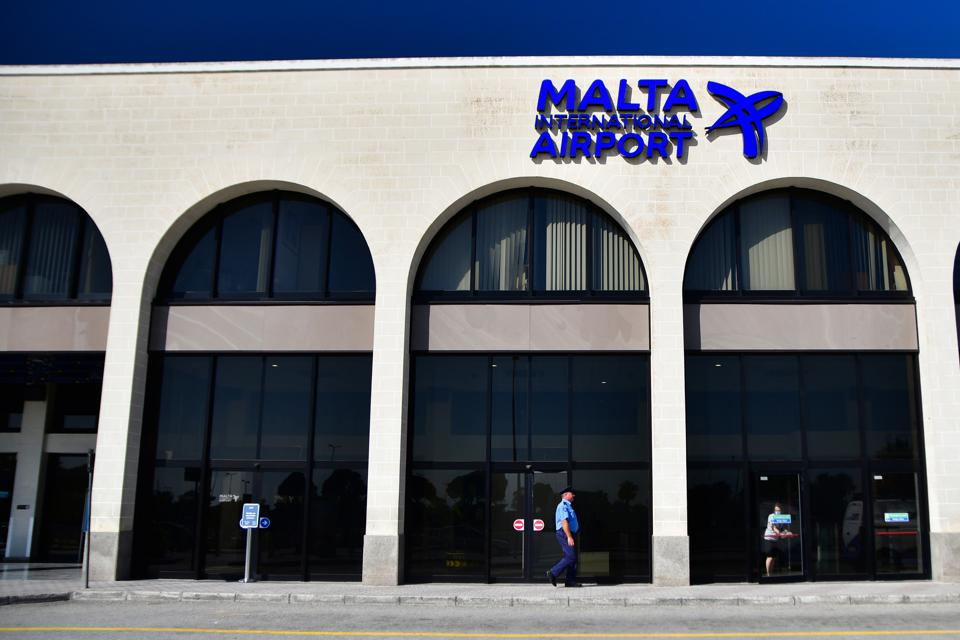 Official walks past Malta International Airport entry