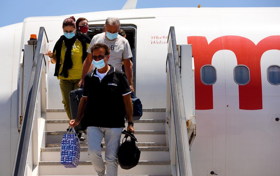 Travelers arrive at Malta International Airport as COVID-19 restrictions ease.
