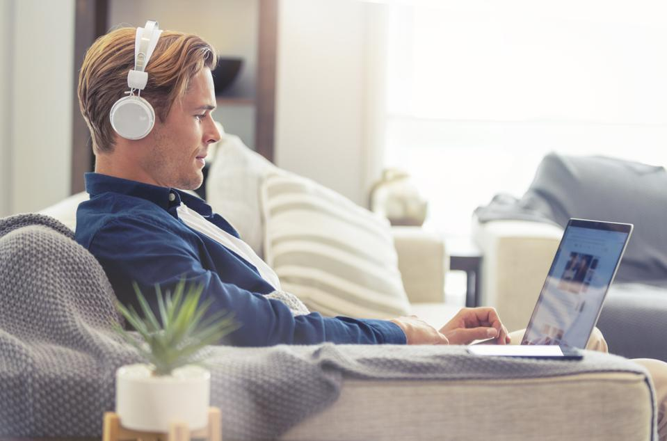Man using a laptop with headphones on the sofa.