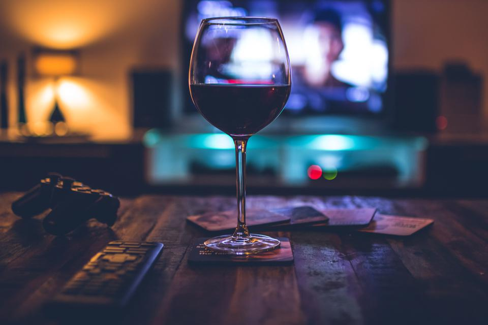 Dark indoor scene with a redwine filled glass in front of a TV