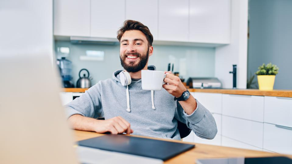 Joyful young web developer drinking coffee while taking break from work in home office