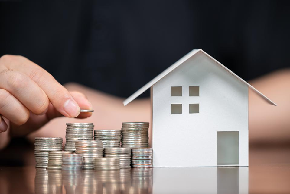 Model houses and stacked coins. Home equity loans. Mortgages and loans.