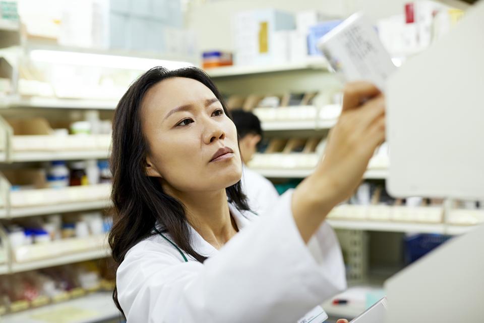 Female pharmacist arranging drugs on shelf
