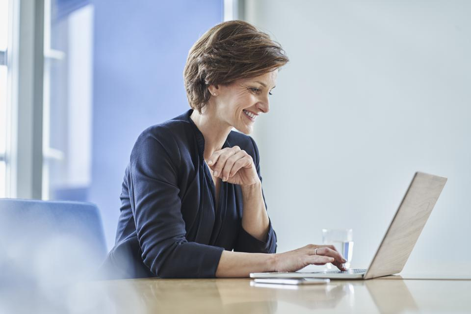Smiling businesswoman using laptop at desk in office