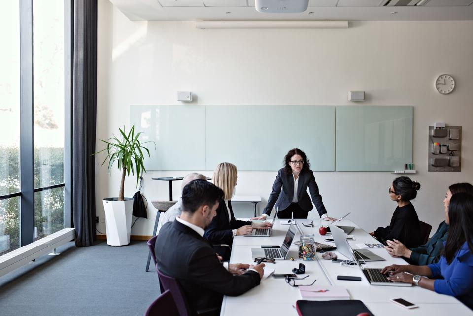 Businesswoman interacting with colleagues sitting at conference table during meeting in board room