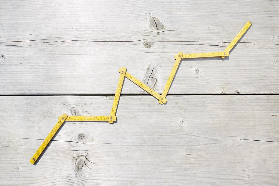 High angle view of a yellow folding ruler in shape of a stock curve on wooden background