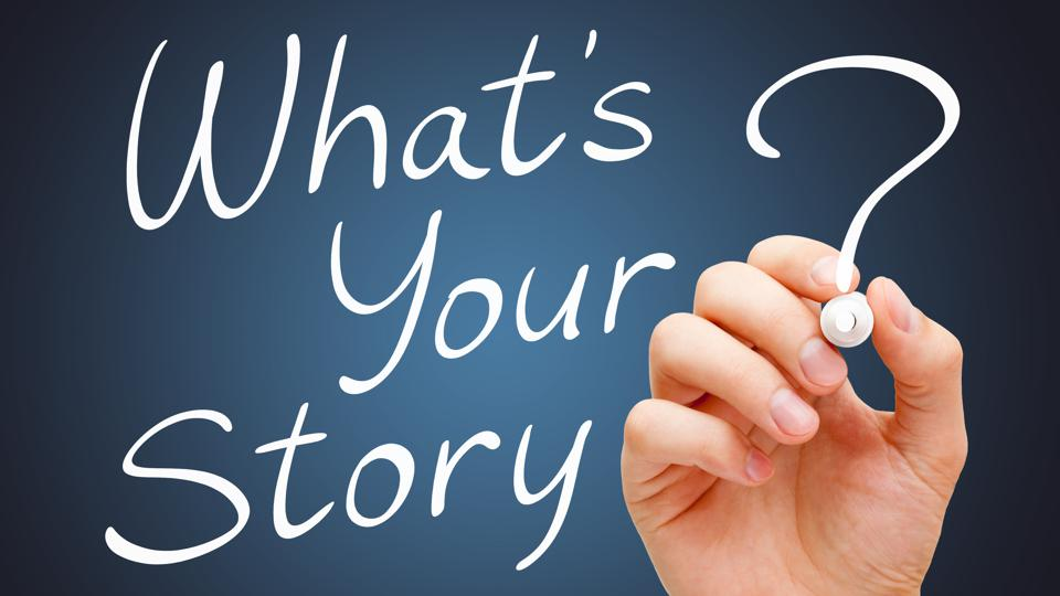 Hand writing What Is Your Story with white marker over dark background.