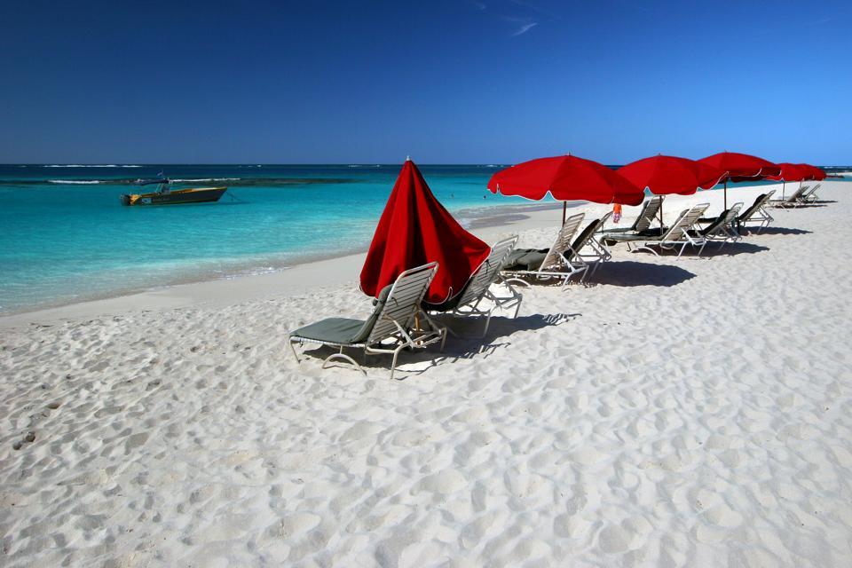 Red beach umbrellas on a white beach