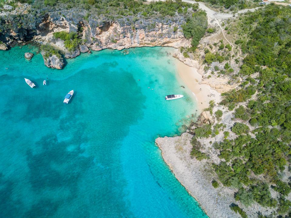 Turquoise water in a bay sheltered by cliffs.