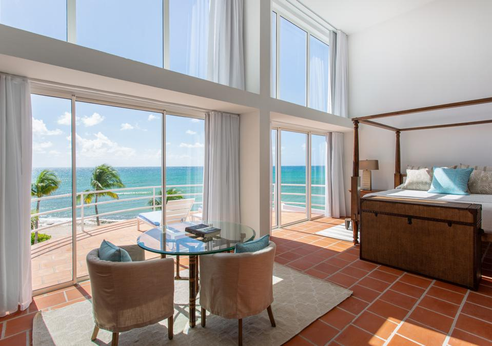 A spacious bedroom overlooking the water with floor to ceiling windows.