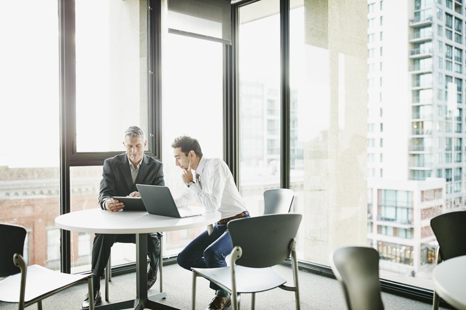 Businessmen reviewing data on digital tablet