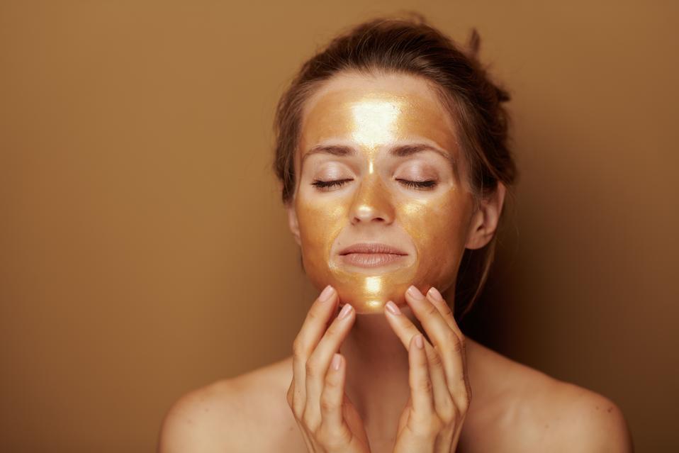 modern woman with golden mask making facial self massage