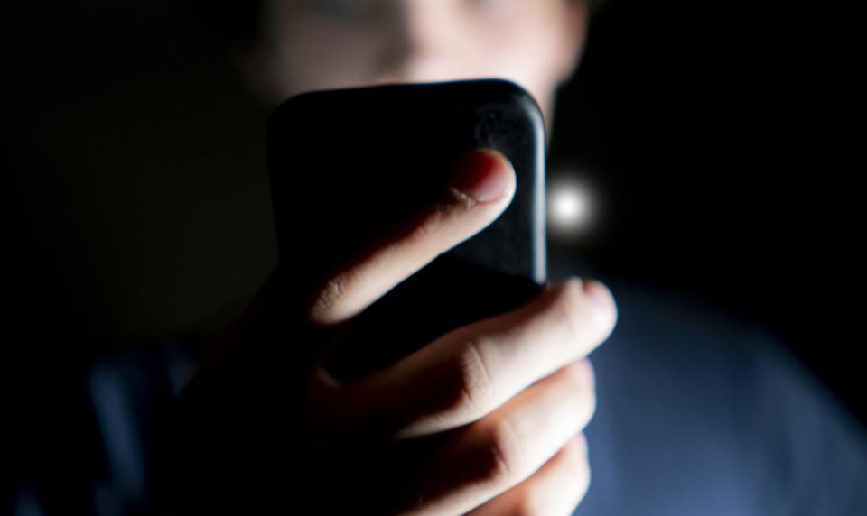 young attractive man use mobile phone late at night in a dark room b