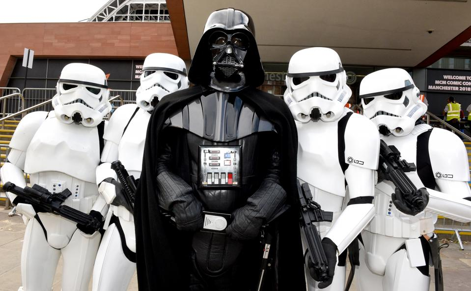 Cosplayers dressed as Darth Vader and Stormtroopers of Star Wars pose during MCM Comic Con 2018