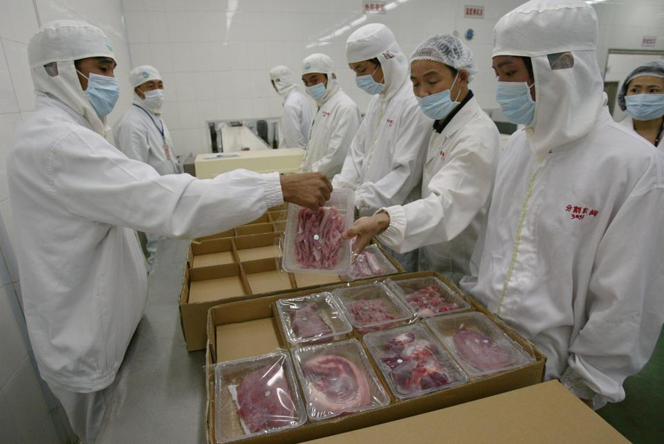 Workers of Dongjin Frozen Meat Co Ltd in protective clothes process the slaughtered pigs (in the packing section) in the frozen pork plant in Huidong, Guangdong, during a media tour by supermarket chain Wellcome.  16 August 2006