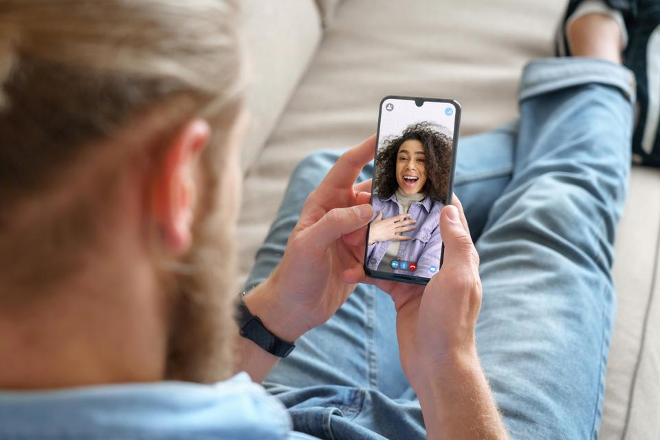 Young man sitting on sofa holding smartphone communicating with african girl friend on mobile screen, making video call using cell phone mobile social media dating app. Video call concept. Over shoulder closeup view