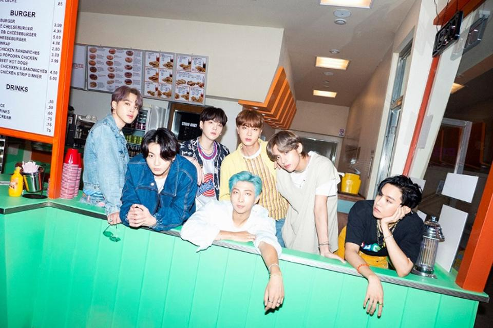 BTS's seven members photographed behind the counter of an old school fast food restaurant