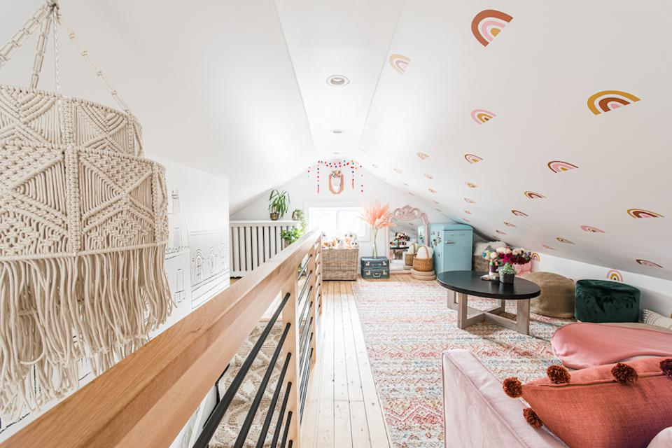 An attic with rainbow decals, a dream catcher and sofas.