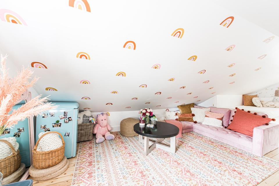 A sloped ceiling area with a lavender sofa, stuffed animals and a table.
