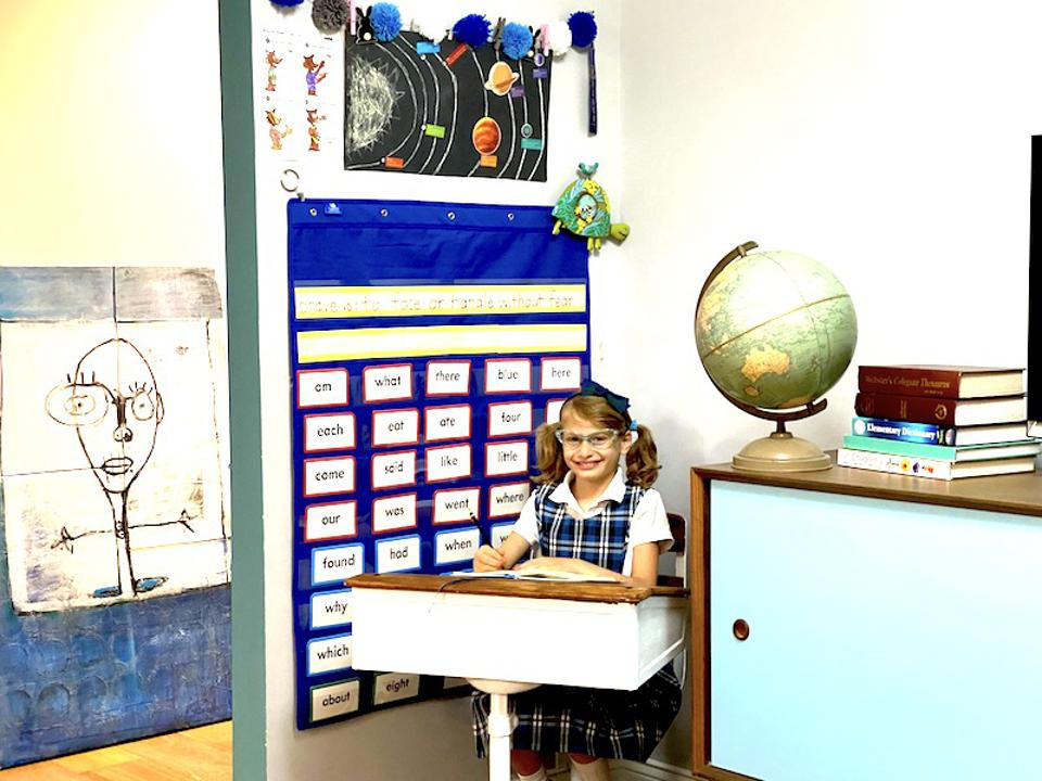 A girl with pigtails at a desk.