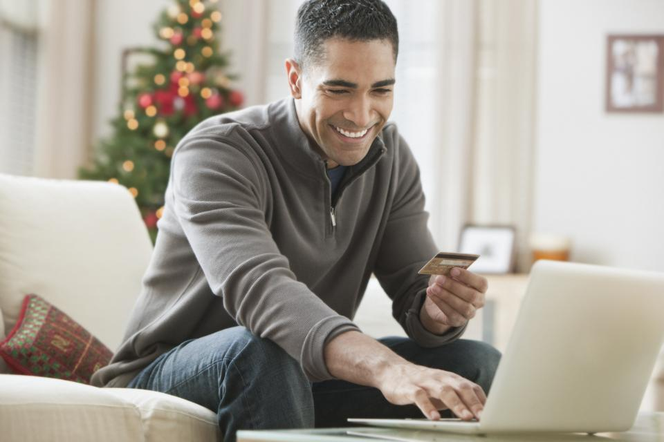 Mixed race man holding credit card and using laptop