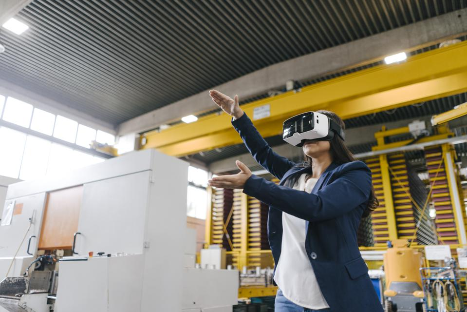 Young woman working in distribution warehouse, wearing VR glasses