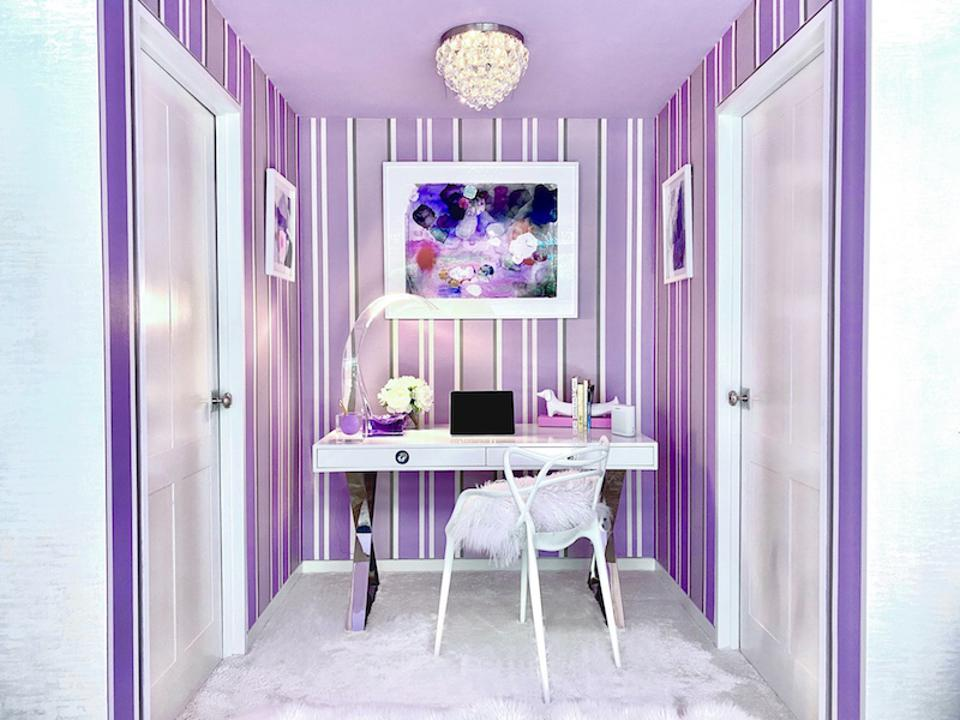Homeschooling nook with purple and white striped wallpaper, a white desk and chair.