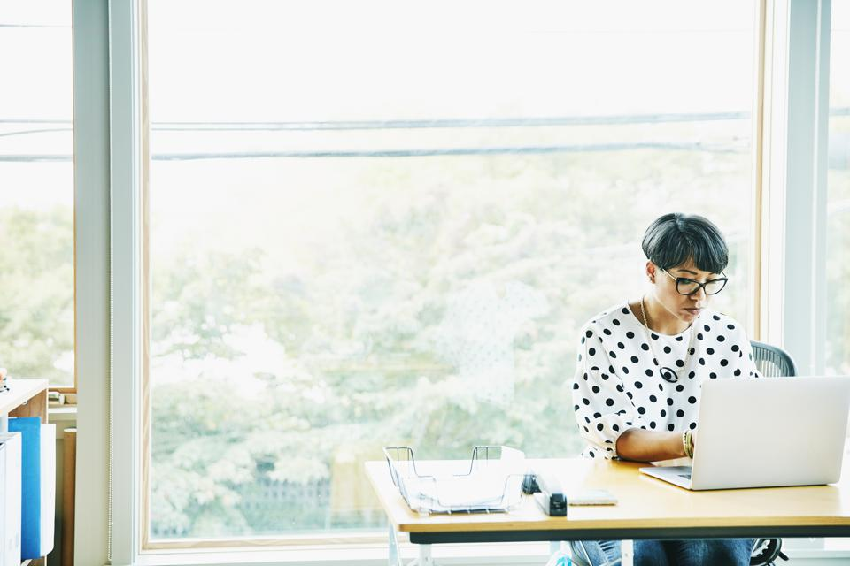 Mature businesswoman working on laptop at desk in creative studio