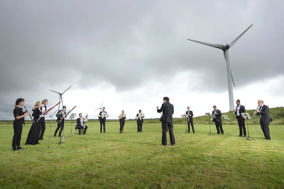A 13-piece wind ensemble from Orchestra for the Earth performs at a wind farm in England.