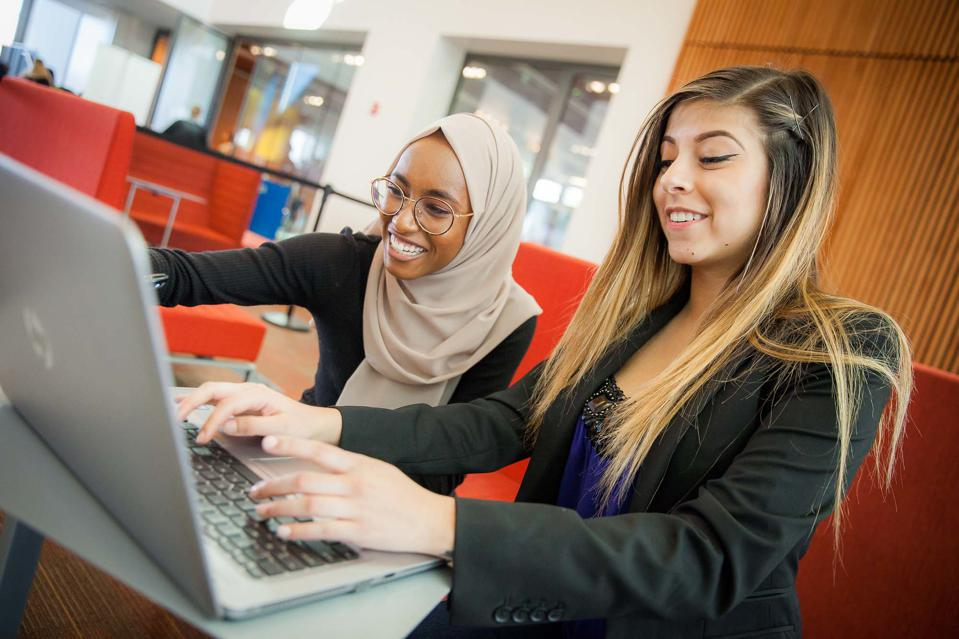 two female students sharing a laptop in a school lounge