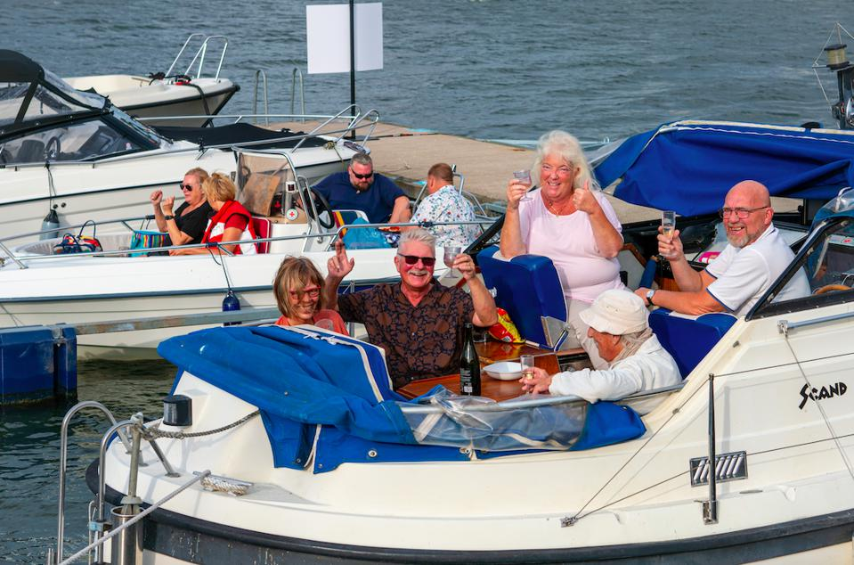 A group of people enjoying drinks and sunshine on their boat in Sweden