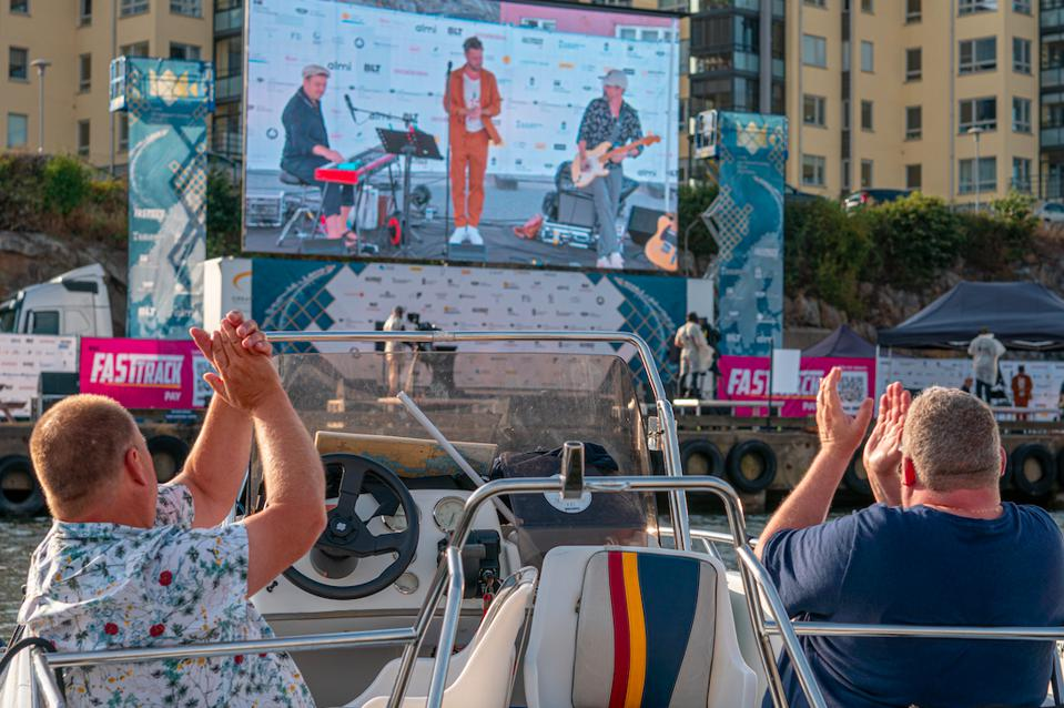 Audience members at Carl Film Festival in Sweden watching alive concert from their boat.