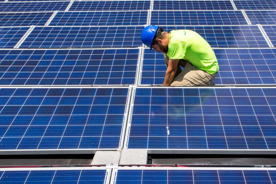 Mike Catanzaro, panel installer at Accelerate Solar, finishes installed electrical wiring at a solar array he recently installed at a job site in East Charlotte.