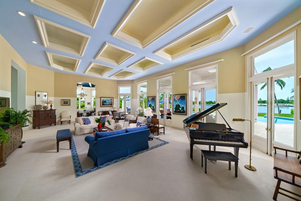 Living room with piano with view of swimming pool