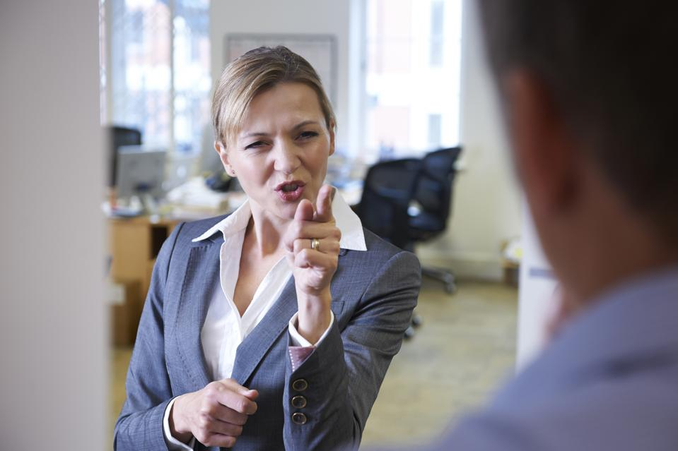 A angry businesswoman yelling at a male colleague