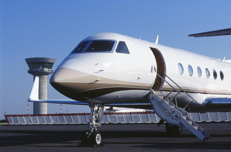 Gulfstream 500 parked with blast fence and air-traffic control-tower behind nose-wheel undercarriage