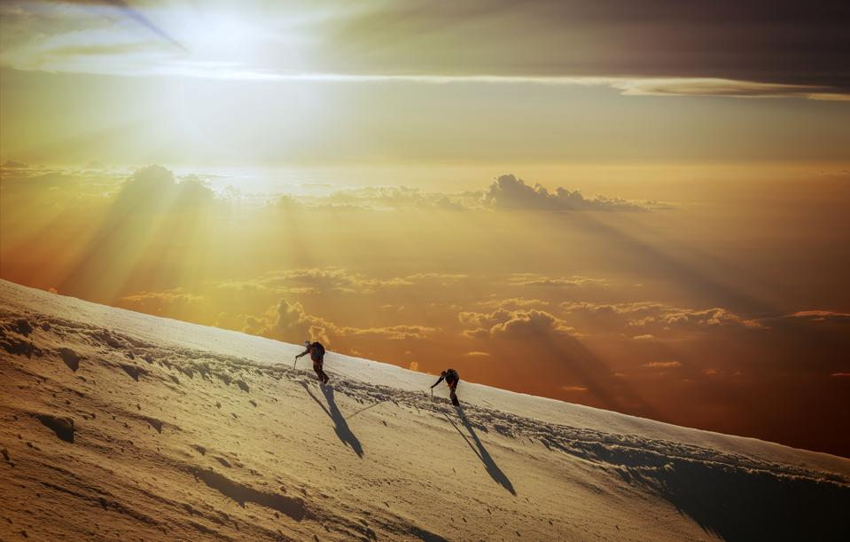 Climbers on a snowy slope at sunrise