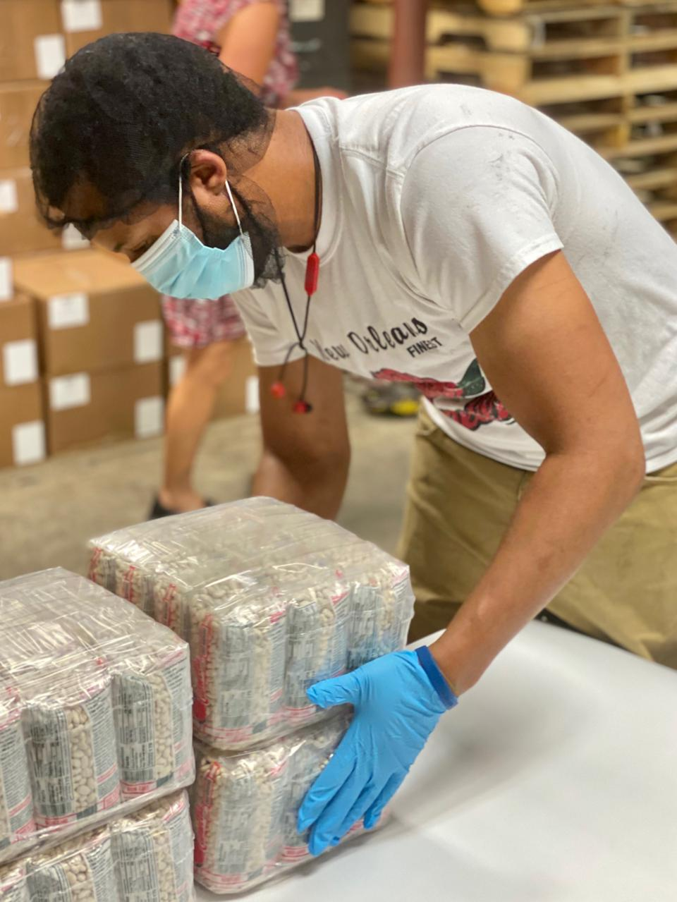 A worker packs bags of red beans for shipping.