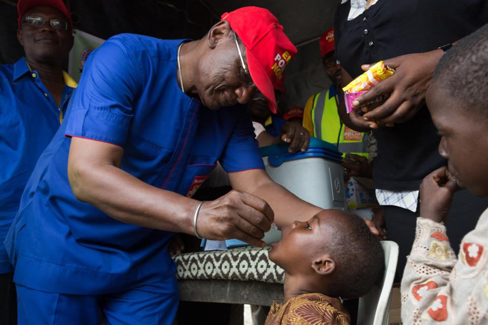 Black man drops polio vaccine drops into young Black boy's mouth