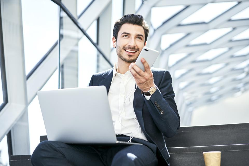 Smiling businessman sitting on stairs wearing earphones using cell phone and laptop