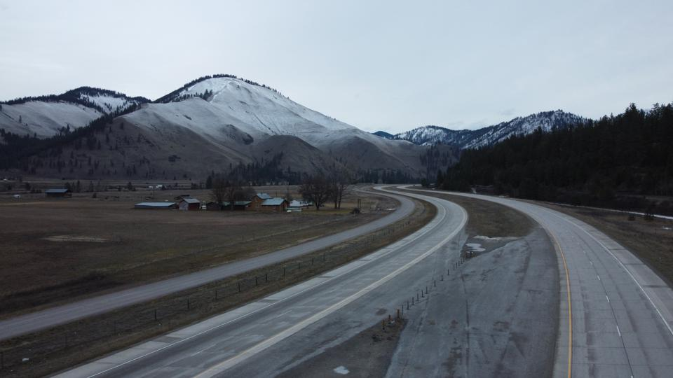 Light snow dusting on a mountain range behind a ranch home sitting on a curvy road