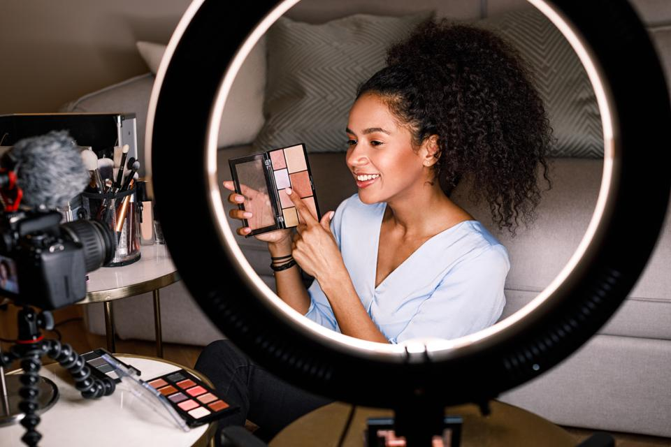 Young Woman Making Video On Make-Up Blog At Home