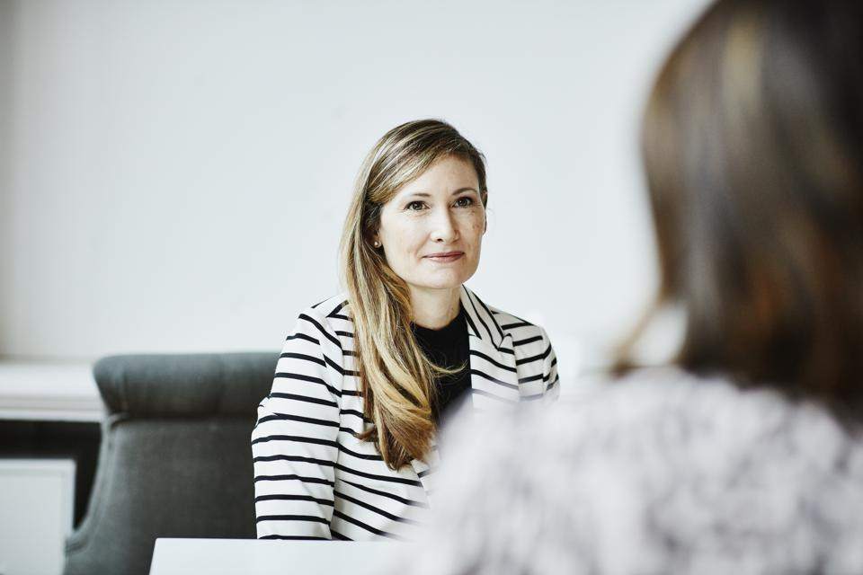 Female financial advisor in discussion with client during meeting in office