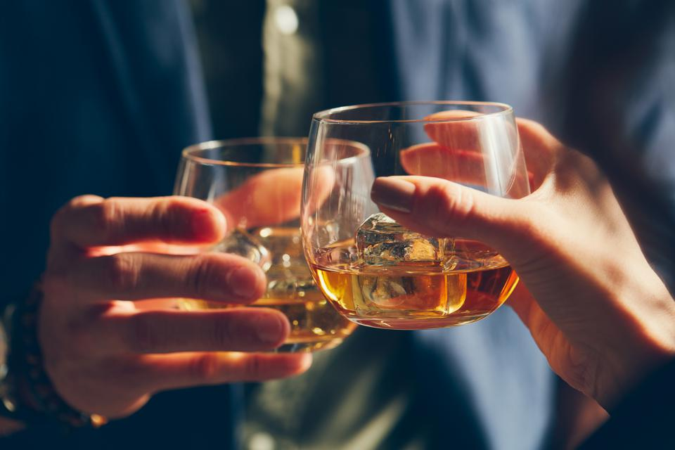 Man and woman celebrating with whiskey glasses