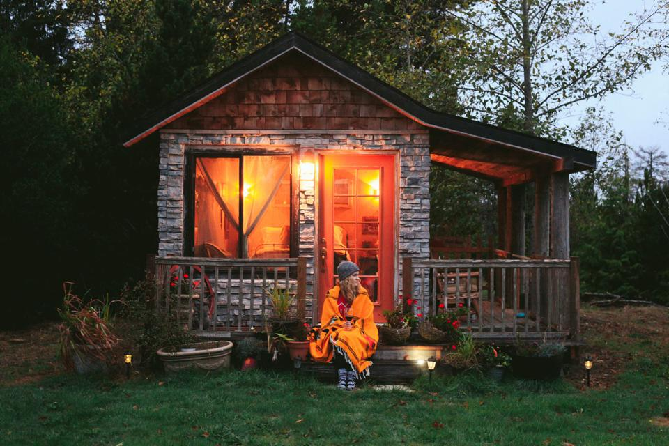 Woman wrapped in orange blanket sits outside cabin at dusk.