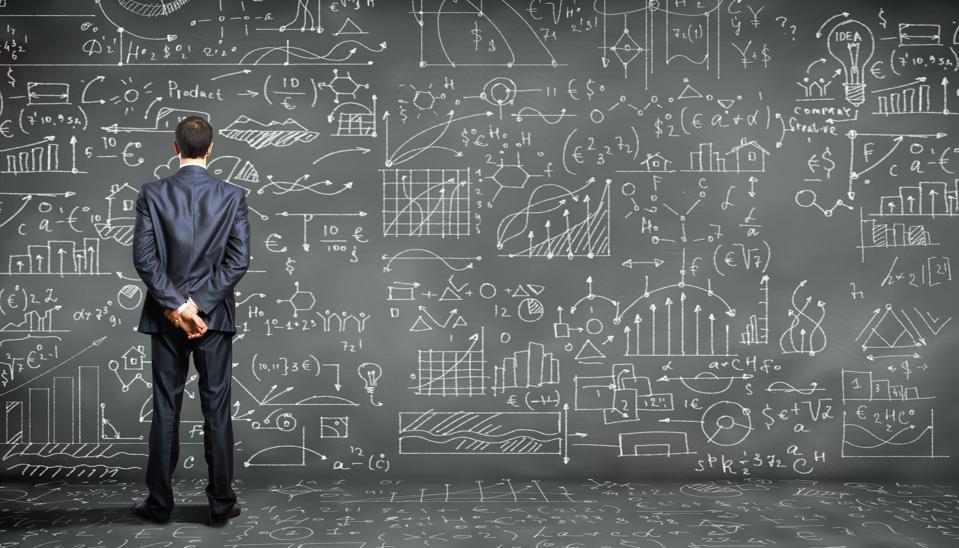 Man looking at a wall filled with mathematical information.